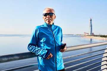 Active pensioner in sportswear listening to music in smartphone outdoors