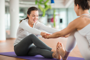 Two girls holding by hands while performing stretching exercise on the floor during yoga workout