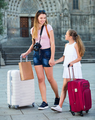 Full length portrait of young mother and daughter travelers walking