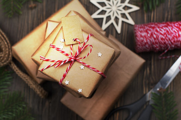 Many Christmas gift boxes. Pile of Christmas presents with decor on dark rustic holiday background. Copy space