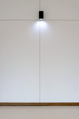 Model lamp on wooden wall in room