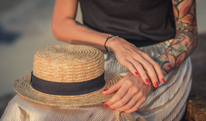 Closeup of a straw hat rests on his knees. Female hand with tattoos correct bracelets. The modern woman