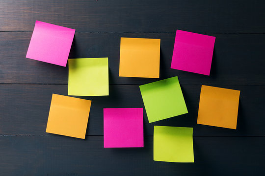 blank colorful sticky notes on wooden background