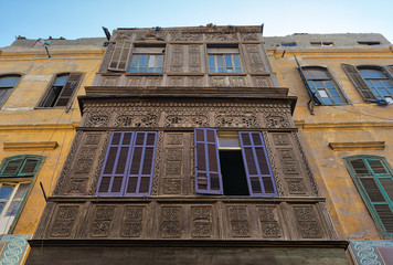 Facade of an old residential building with wooden ornate engraved wall, yellow painted wall, and violet painted wooden windows in an old street, Old Cairo, Egypt