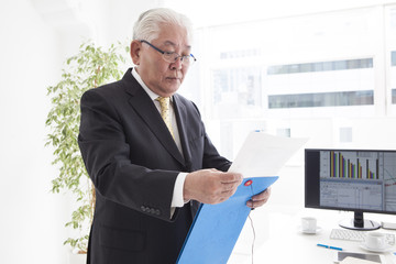 The old man is looking over the business documents