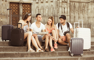 four glad traveling young people searching for direction using paper map in European town