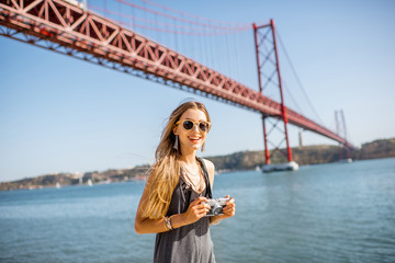 Portrait of a young woman tourist with photo camera standing in front of the famous iron bridge traveling in Lisbon city, Portugal