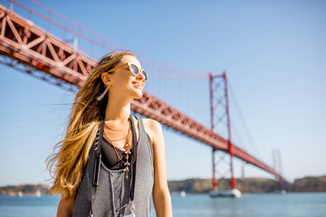 Portrait of a young woman tourist in front of the famous iron bridge traveling in Lisbon city, Portugal