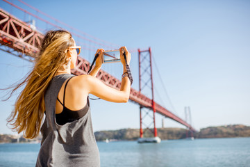 Young woman tourist photographing famous iron bridge in Lisbon city, Portugal