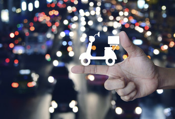 Motor bike icon on finger over blurred colourful night light city with cars, Business delivery service concept