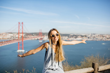 Woman having fun flying with hands on the beautiful landscape view background with iron bridge and river in Lisbon city, Portugal
