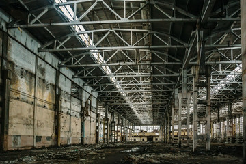 Abandoned large industrial hall or warehouse with garbage, manufactory factory