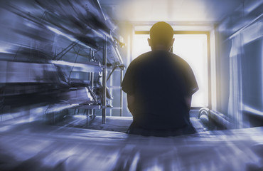 Man sitting on the hospital bed looking through the window, concept of dying patient