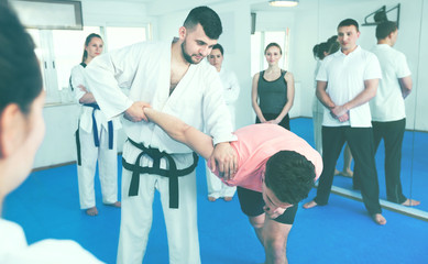 Coach showing new submission hold in taekwondo class