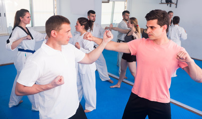 Boys with girls are practicing new karate moves in pairs