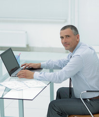 smiling businessman sitting at Desk and looking at camera