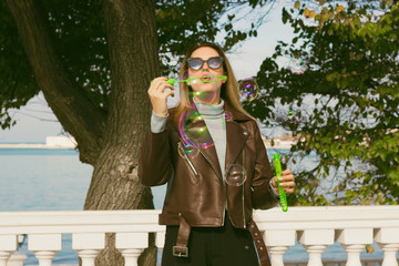 Young pretty girl blows soap bubbles, outdoor