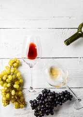 Image on top of wine glasses, black and green grapes, bottle
