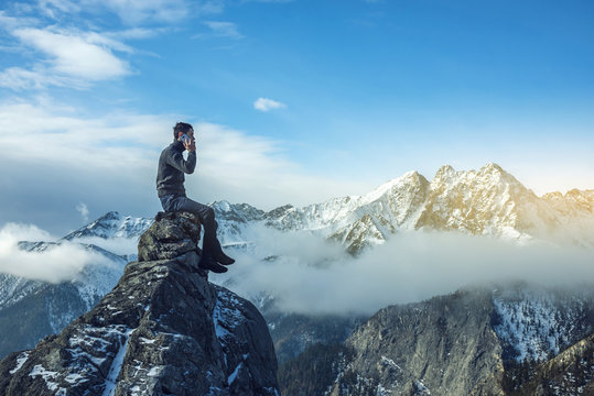 Young man in a sweater with phone in hand on the top of a snowy mountain. Concept availability of mobile connection