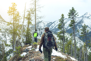 Men hikers with backpack on top of the mountain looking at the snow slope. Concept of motivation and goal achievement