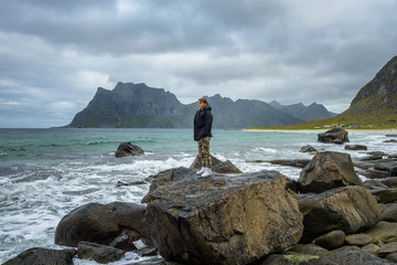 Wall Mural - Boy stands on a big rock and enjoys the view over a beach in Norway