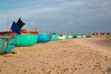 Traditional Vietnamese fishing coracles on beach, boats in fishing village