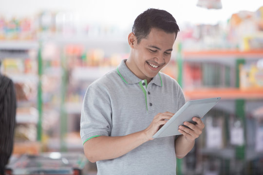 male supermarket owner with tablet pc