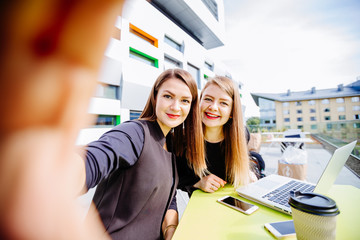 Two business woman taking selfie while sitting in cafe outdoor. Education, lifestyle and people concept.