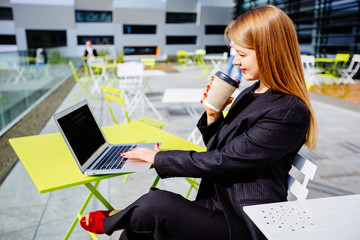 Gorgeous swede female freelancer dressed in classic suit working with tablet computer on open ait cafe terrace business center.