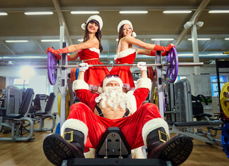 Sports Santa Claus with girls in Santa's costumes in the gym on Christmas and New Year.