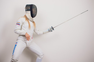 woman wearing fencing suit practicing with sword against grey vignette