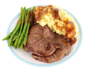 Fried venison steak meal with mashed potatoes and asparagus isolated on a white background