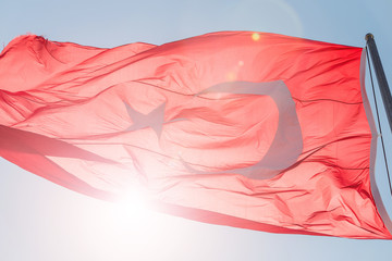 National Flag of Turkey over Blue Sky with sun flare