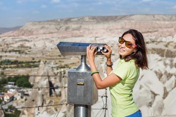 Traveler Woman looking through touristic telescope in Cappadocia, Turkey