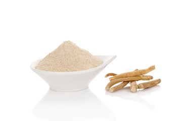 Ashwagandha powder in spoon with roots