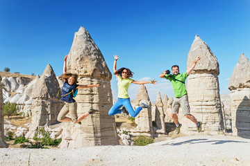 Group of happy caucasian Friends jumping and having fun while travelling among Cappadocia fairy chimneys at summer