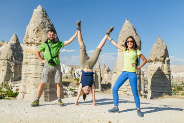 Group of happy caucasian Friends having fun while travelling among Cappadocia fairy chimneys at summer