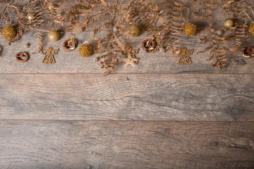 Christmas golden rustic decoration on wooden background, close-up, top view, flat lay
