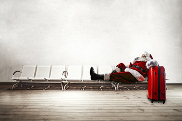 Old red santa claus siting on chairs. White wall background for your text ora wooden floor for your product.
