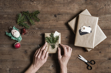 Woman wrapping Christmas presents on wooden table