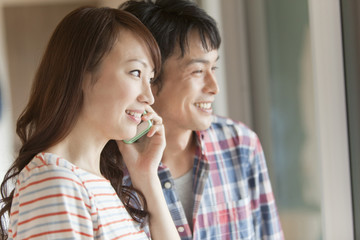 携帯電話で話をするカップル