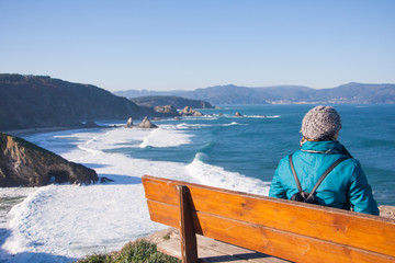 A woman admires the panorama from the top of a cliff sitting on a bench. Loiba cliffs, Galicia