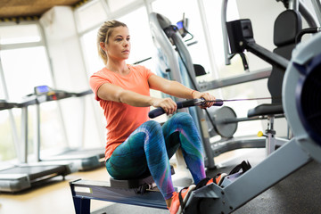 Young blonde woman working on rowing machine