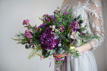 A wedding bouquet of purple hydrangeas, olive branches and succulents in the bride's hands.