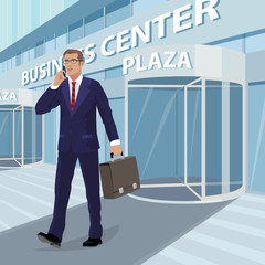 Young businessman with glasses and blue business suit comes out of business center with briefcase in his hand and talks on phone. Man on background of building facade