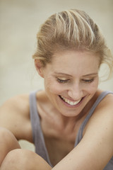 Portrait of laughing blond woman sitting on the beach