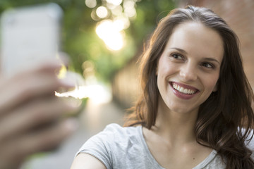 Portrait of happy young woman outdoors taking a selfie