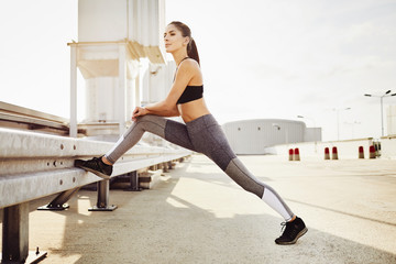 Young woman stretching during city workout