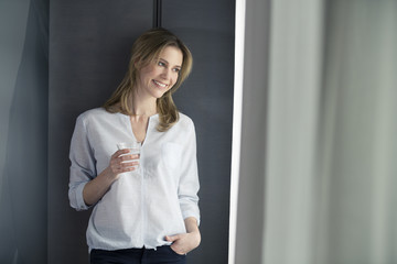 Smiling woman holding glass of water looking out of window