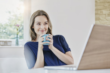 Smiling woman at home with coffee mug and laptop